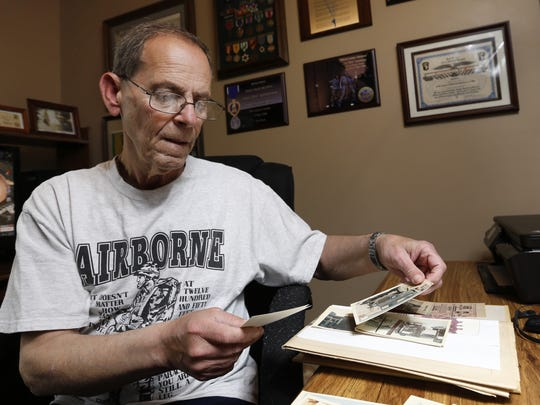 Vietnam veteran John Vandehaar of Des Moines looks through photographs May 15 that he took during the Vietnam War.