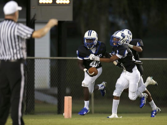 Godby Cornelius Brown, left, celebrates with teammates after returning an interception for a touchdown against Leon at Cox Stadium on Friday.