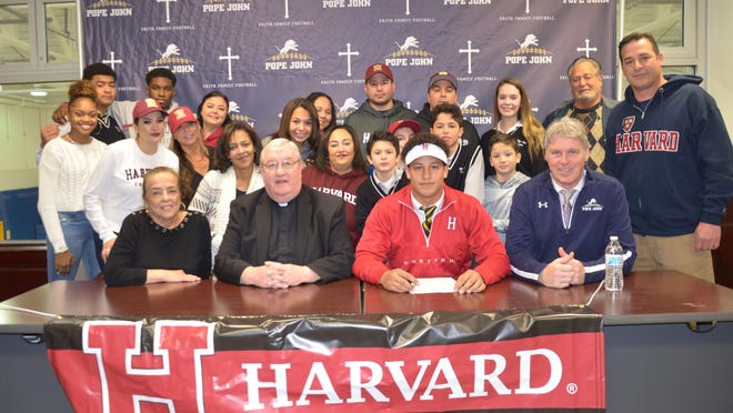 Pope John XXIII Regional High School senior Jake Brown, sitting in red, signed his National Letter of Intent to play football for Harvard University. Sitting with Brown, from left, are Brown's grandmother Cristina Brown, Pope John President and Principal Monsignor Kieran McHugh and Pope John head coach Brian Carlson. Standing in the second row are Kiiantay Brown, Tina Brown, Allison Brown, Brown's mother Monique Brown, Devin Brown, Evelyn Santos, Sean Brown, Eddie Brown, Luke Brown, and James Brown. Standing in the third row are Terrance Jones, Jhadir Charles, Danielle Diaz, Lee Brown, Sean Brown, Cristina Lloyd, Lou Brown and Philip Brown.