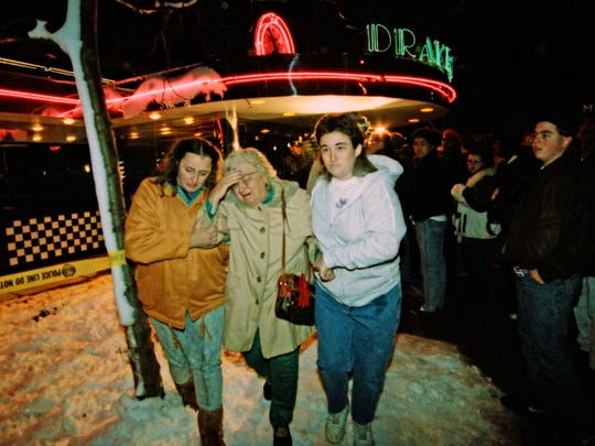 Grief-stricken Phyllis Burnett is taken from the Drake Diner where her son, Tim Burnett, 28, and Cara McGrane, 25, who were both employees at the restaurant, were shot and killed Nov. 29, 1992.