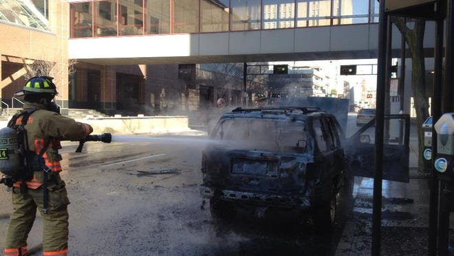 Firefighters douse a an SUV that caught fire Thursday morning Downtown.