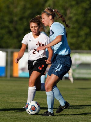 Lansing Catholic's Abigail Gilmore, right, controls the ball against Jonesville's Jessica Kirk in their regional game, Tuesday, June 6, 2017, in Williamston.