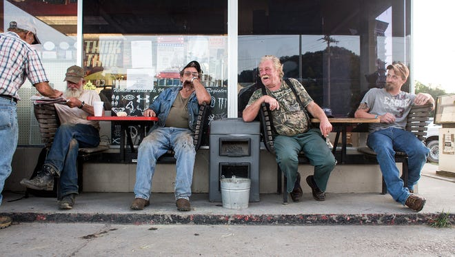 """Tom Orr, left, Joe Waldroup, Roy Grooms and Robert Jordan sit outside Time-Out gas station in Robbinsville Wednesday night, Aug. 27, 2014. Waldroup and Grooms are both former moonshine makers, and Grooms appears on the Discovery Channel show """"Moonshiners"""". They both continue to work construction jobs here and there, they said. """"The smartest people that come from Graham County are the ones who graduated and got out of here,"""" Waldroup said of the county with limited jobs. Robbinsville's main industry, Stanley Furniture, closed in July, putting more than 400 people from the region out of work."""