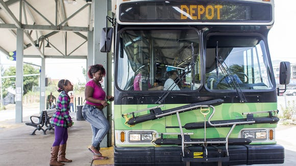Omani Davis, 10, left, and mom Crystal Davis, center, board the S4S bus at the ART Station, or Asheville Transit Center, on Coxe Avenue in Downtown Asheville, Monday last year. Asheville Transit will offer free bus rides on Wednesday
