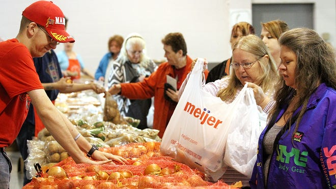 Volunteers distribute food during a Salvation Army produce market in Marion. The organization has been forced to shut down its soup kitchen until further notice due to concerns about spreading the coronavirus. Capt. Kristin Price said participants in last week's soup kitchen did not follow Ohio Department of Health guidelines to remain six feet apart during the event.