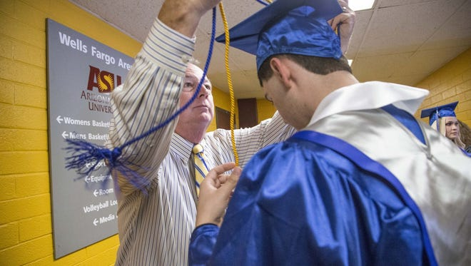 Frank Mitcham, a Balfour representative, helps Nick Yates , a graduate of Mesquite High School, with his honor cords during graduation at Wells Fargo Arena on May 20, 2015.