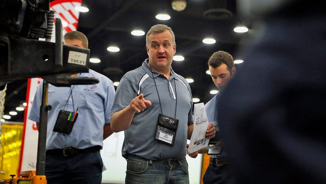 Dan Trahey gives some helpful hints and instruction to a group of competitors at the automotive refinishing technology area during the Skills USA Championships held at the Kentucky Expo Center, Wednesday, June 24, 2015.