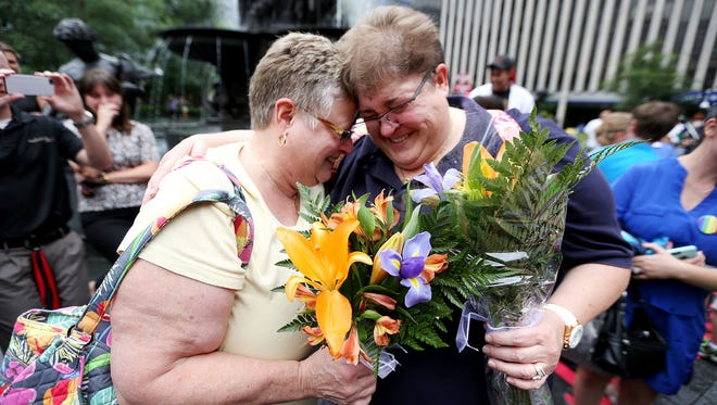 """Barbara Eisenhardt (left) and Tiffany Wahl of Sycamore Township embrace before they are married by Mayor John Cranley at Fountain Square on Friday. They were one of five same-sex couples to be married after the U.S. Supreme Court legalized same-sex marriages nationwide. """"I am speechless at this point. I didn't think I would see this in this life time,"""" Gisonhardt said."""