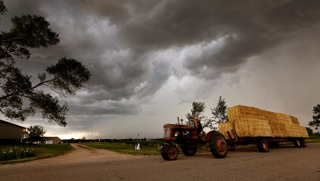 A tractor pulls hay bails as a storm passes overhead.