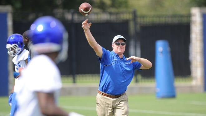 Head coach Mark Stoops throws a pass during the University of Kentucky Football fan day at the Nutter Field House in Lexington, Ky., on Saturday August 8, 2015. Photo by Mike Weaver