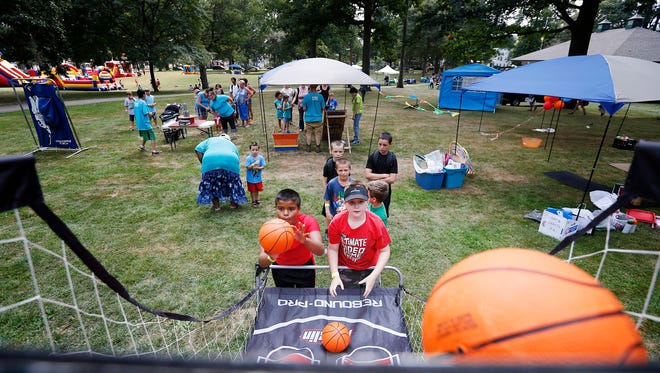 Isaiah King, 11, left, and Kamron Bellinger, 10, both of Elmira compete to see who can make more baskets Saturday at the September Fest at Grove Park in Elmira.
