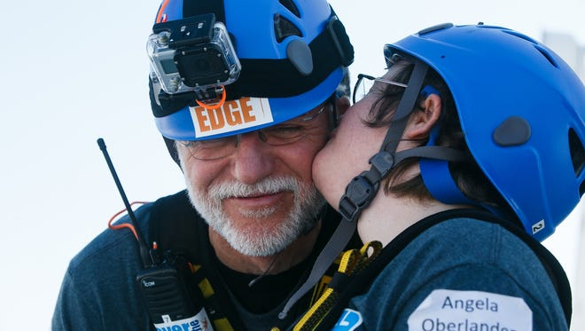 Special Olympic athlete Angela Oberlander, right, gives her father Al, left, a kiss on the cheek before they rappel down the side of the Financial Center during the Over the Edge for Special Olympics fundraiser in downtown Des Moines on Wednesday, September 16, 2015.
