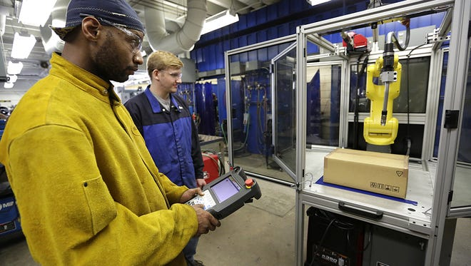 Zerick Byrd of Fond du Lac and Lucas Hellmer of Greenbush get the feel for controlling a new robotic arm used for welding, Thursday morning, in a classroom at MPTC. Thursday September 17, 2015.