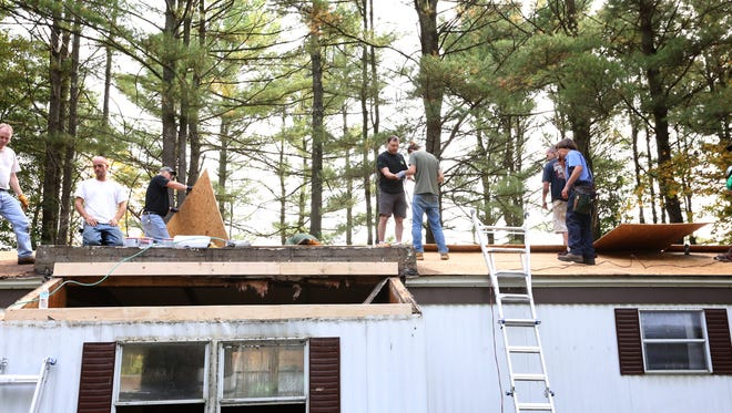 Men repair Roger Cox's roof Saturday morning by nailing down plywood.