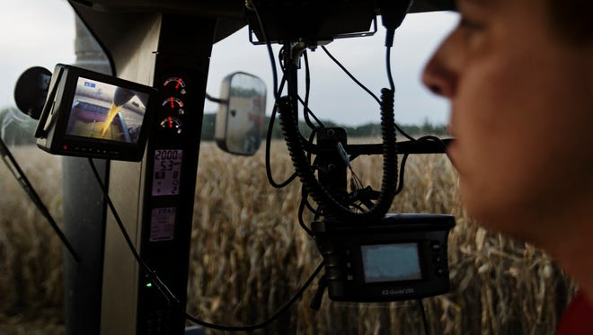 A camera shows a farmer how full the grain bin is as he drives next to a combine.