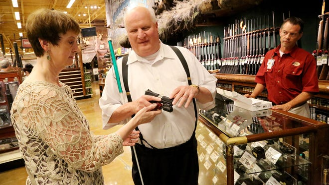 In this file photo, Michael Barber and his wife Kim shop for a gun with the help of Bass Pro Shop Operation's Manager Todd Godfrey in Des Moines, Iowa. Kim is showing him how the gun lock fits on the gun.
