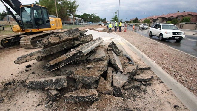 Large chunks of asphalt paving are stacked along the northbound lanes of George Dieter Drive near the intersection with Rex Baxter Drive after a large sinkhole developed there Saturday morning in East El Paso.
