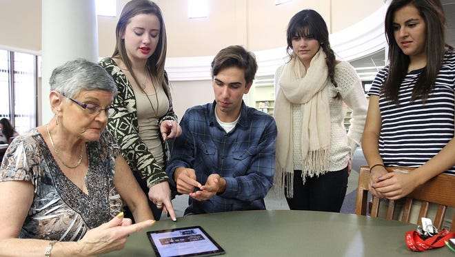 Harding students show Royce Farson (left) how to use the fleshy tip of the finger to type when using a pad device. which has a different feel and response than the traditional keyboard that Farson is accustomed to. The students (from left) Lauren Nelson, Phillip Nicol, Shelbie Howard and Daisy De La Paz, will visit the Marion Senior Center in November to teach seniors to use new devices to access email and social media.