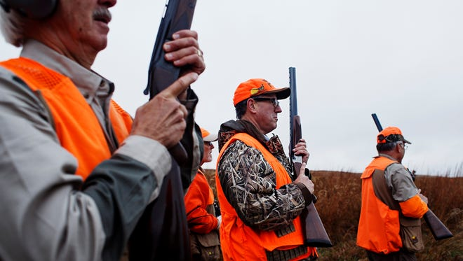 Republican presidential candidate Rick Santorum walks through the field with other hunters during a pheasant hunt at The Hole N the Wall Lodge on Saturday, October 31, 2015 in Akron, Iowa.