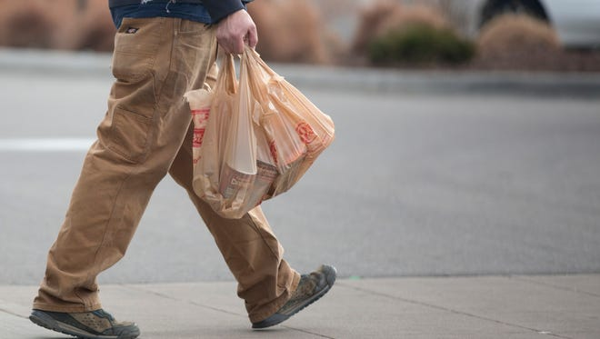 People carry plastic bags full of groceries out of King Soopers in north Fort Collins in March 2014.