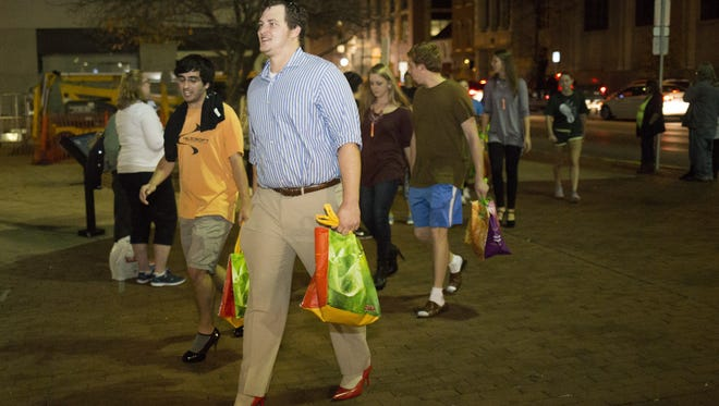 Jason Sneeringer, of York Township, center, takes part in the Walk a Mile in Her Shoes event in York. Men walk in heels through downtown York during the fundraiser for ACCESS-York and Victims Assistance Center.