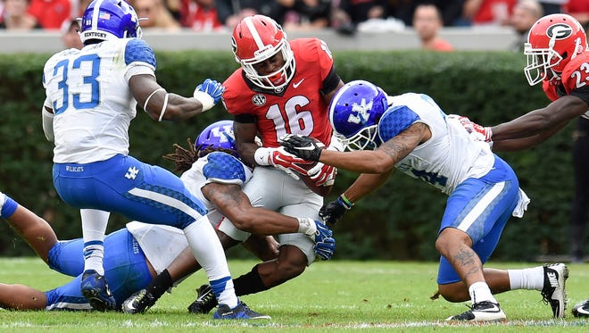 Nov 7, 2015; Athens, GA, USA; Georgia Bulldogs wide receiver Isaiah McKenzie (16) fumbles as he is hit by Kentucky Wildcats cornerback Blake McClain (24) during the first half at Sanford Stadium. Mandatory Credit: Dale Zanine-USA TODAY Sports