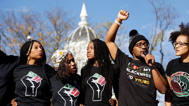 Concerned Student 1950, led by University of Missouri graduate student Jonathan Butler, second from right, speaks following the announcement that University of Missouri System President Tim Wolfe would resign Monday, Nov. 9, 2015, in Columbia, Mo. Wolfe resigned Monday with the football team and others on campus in open revolt over his handling of racial tensions at the school. (Sarah Bell/Missourian via AP) MANDATORY CREDIT