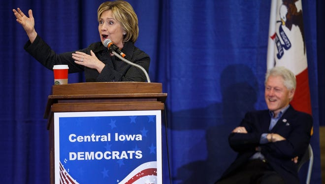Hillary Clinton speaks at Iowa State University Sunday as her husband, former President Bill Clinton, looks on.