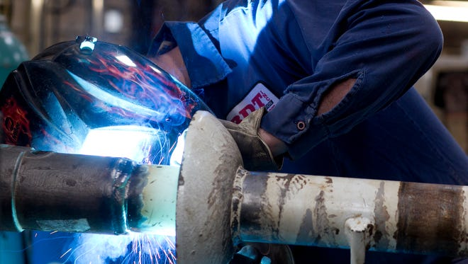 Welder Jarrod Barton of Wisconsin Rapids works on welding a piece of equipment at BDT Inc. in Wisconsin Rapids, Friday, Nov. 13, 2015.