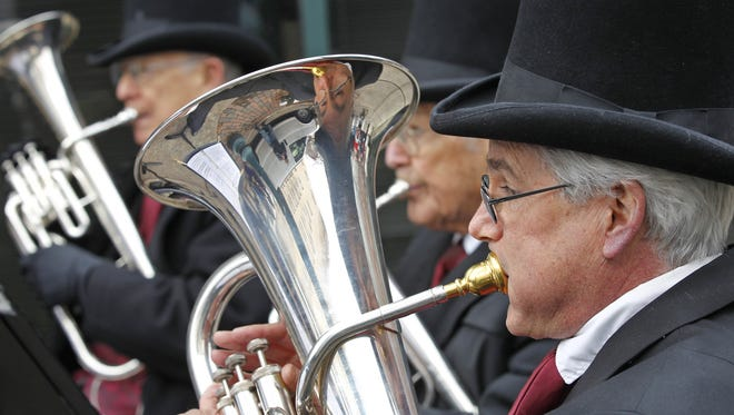 Steve Bell, foreground, and the other members of Vintage Brass perform holiday favorites during a Holiday Farmers Market as part of the 17th annual Dickens of a Christmas Saturday, December 6, 2014, on Main Street in downtown Lafayette. Vintage Brass is a sub-group of Lafayette Citizens Band. Dickens of a Christmas is presented by Greater Lafayette Commerce.
