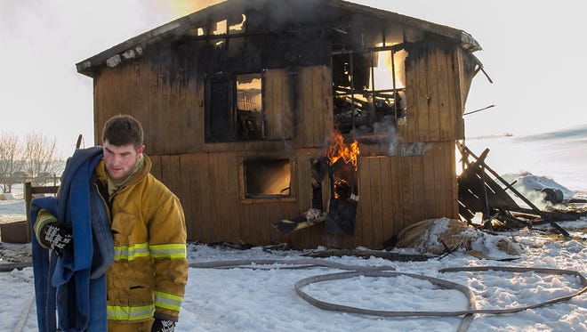 This photo taken Feb. 7, 2014, shows firefighter Cody Bumbaugh of Mont Alto Fire Department carrying a fire hose during a barn fire on Altenwald Road in Guilford Township. Mont Alto Fire Department was one of several local fire companies to win a grant in October 2018 from the Pennsylvania Department of Conservation and Natural Resources.
