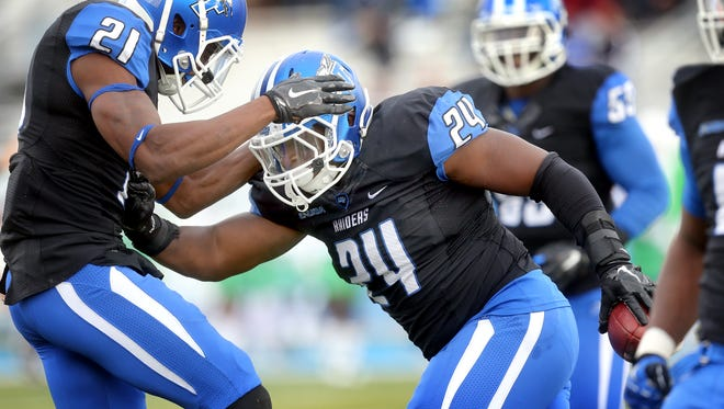 MTSU's Jamarcus Howard (21) celebrates Cavellis Luckett's (24) fumble recovery against North Texas in the first half of an NCAA college football game against Marshall, on Saturday, Nov. 21, 2015, in Murfreesboro, Tenn.