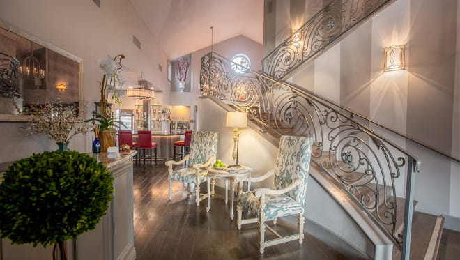 The lobby at the recently renovated Chateau at Lake La Quinta features an elegant staircase and access to the bar just beyond.