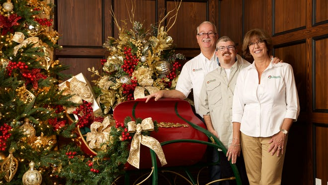 Bill and Marji Kilgus pose with their son Billy in front of a Christmas sleigh they decorated at The Club at Olde Cypress in Naples.