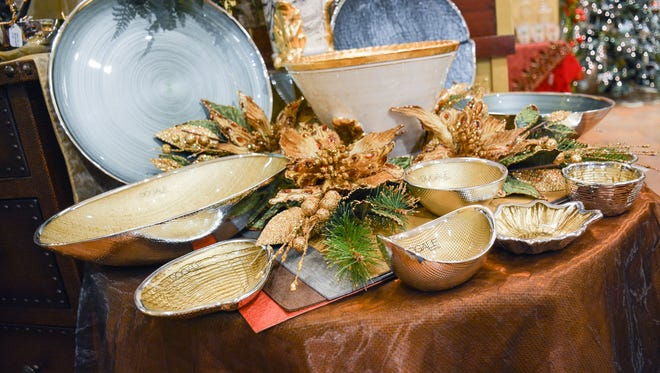 Doagle serving pieces in golds, blues and greens trimmed in holiday silver highlight this holiday table. Available at Jody's.