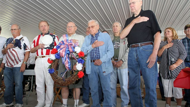 Former service men and women stand behind a wreath while taps is played during a Veteran's Day Celebration at the Marion County Fair on Friday. All veterans in attendance were recognized by name as the Marion Presidential Brass Band played service branch anthems following a free breakfast for veterans and their guests.