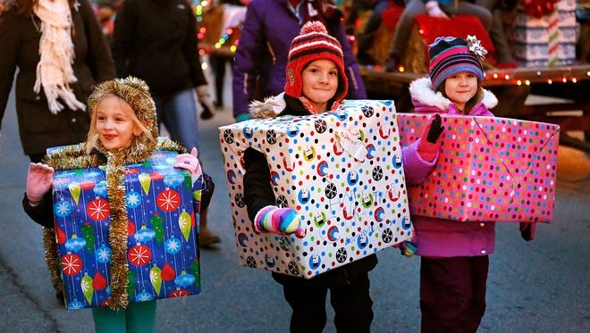Dressed as Christmas gifts, Lillian Birschbach, Mackenzie Williams and Ella Seyfert walk in the 2015 Fond du Lac Christmas Parade of Lights, Saturday night, representing Girl Scout troops 8227 and 8043.