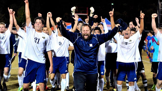 Josh Martin (in the navy coat) celebrates after Roberson won the NCHSAA 4-A soccer championship in 2013.