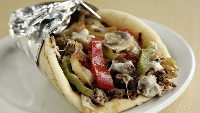 Shaved rib-eye steak and grilled onions and peppers are served with cheese in pita bread.