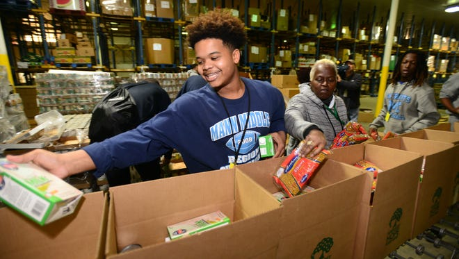 Quintez Griggs and other J.L. Mann High School basketball teammates pack boxes of food at Harvest Hope on Friday, Jan. 16, 2015. The food bank is one local agency that receives funding from donations made to the Holiday Sunshine Fund.