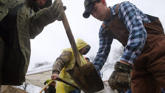 Jesse Nelson, left, 32, of Barnhart, Mo., and Ryan Morris, 20, of Imperial, join other volunteers in making sandbags as the Mississippi River rises after several days of rain in Kimmswick, south of St. Louis on Sunday, Dec. 27, 2015. (Cristina M. Fletes/St. Louis Post-Dispatch via AP) MANDATORY CREDIT