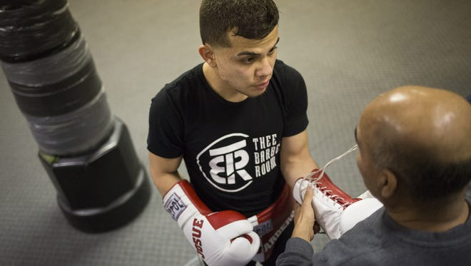 Trainer Julio Alvarez, 65, of Thomasville, right, ties the gloves of Josue Alfaro, 20, of New Oxford, prior to a sparring session this month. Alfaro hopes to make his professional debut in February.