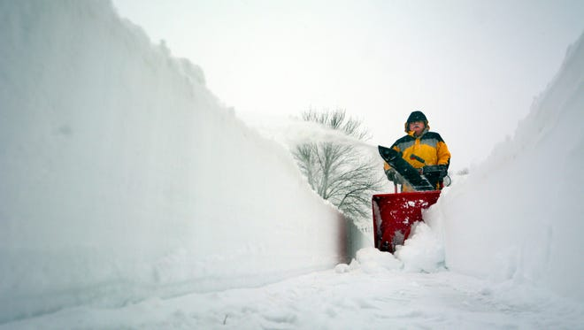 Jim Beamer clears a trench near his Texas Avenue home in York City Saturday, Jan. 23, 2016. Snowplows were moving snow onto the sidewalk near his home. Bil Bowden photo.