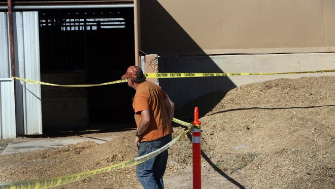 A man walks by yellow caution tape placed around a horse barn area on Monday at Sunland Park Racetrack & Casino. Horse racing at the track has been stopped because of an equine virus.