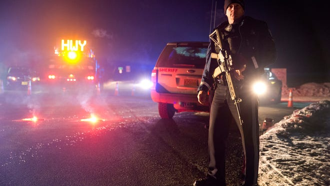 "Sgt. Tom Hutchison stands in front of an Oregon State Police roadblock on Highway 395 between John Day and Burns by Oregon State police officers Tuesday, Jan. 26, 2016. Authorities say shots were fired Tuesday during the arrest of members of an armed group that has occupied a national wildlife refuge in Oregon for more than three weeks. The FBI said authorities arrested Ammon Bundy, 40, his brother Ryan Bundy, 43, Brian Cavalier, 44, Shawna Cox, 59, and Ryan Payne, 32, during a traffic stop on U.S. Highway 395 Tuesday afternoon. Authorities said another person, Joseph Donald O'Shaughnessy, 45, was arrested in Burns. In a statement, the FBI said one individual ""who was a subject of a federal probable cause arrest is deceased."""