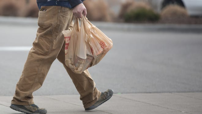 A man carries plastic bags full of groceries  out of King Soopers.