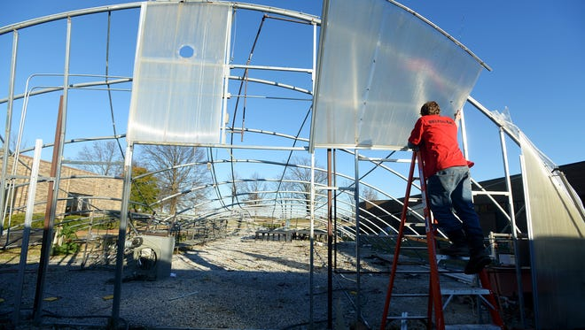 Austin Howard removes a panel from the greenhouse that used to stand at Crockett County High School. The greenhouse suffered damage after an EF-1 tornado touched down in the area Tuesday evening.
