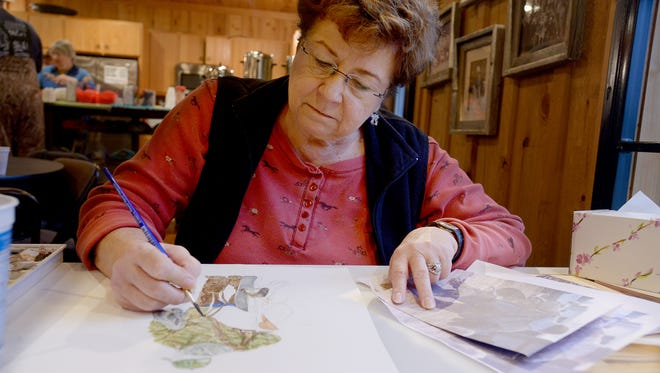 Mary McAuslin paints, using watercolors, from a photo taken at the National Bird Dog Championship on Monday morning. McAuslin has been painting at the championship for seven years.