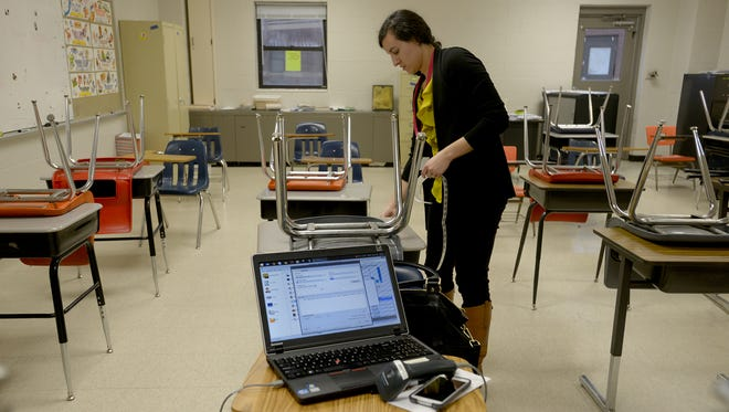Holly Leisey places inventory stickers on desks in a classroom at Northeast Middle School on Monday evening.