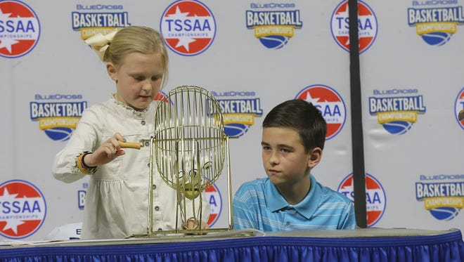 Cari Beth Gillespie, 9, left and Holt Gillespie, 11, draw numbers, on Tuesday at MTSU to determine the pairings for the Class AAA bracket for the TSSAA Boys Basketball State Championships.